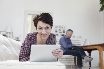Deutschland, München, Frau mit Tablet PC, während Mann mit Laptop im Hintergrund