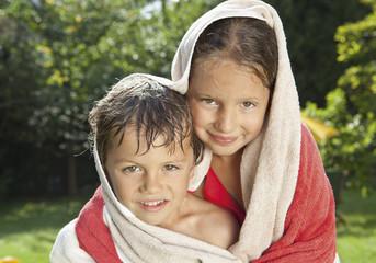 Deutschland, Junge und Mädchen im Handtuch eingewickelt