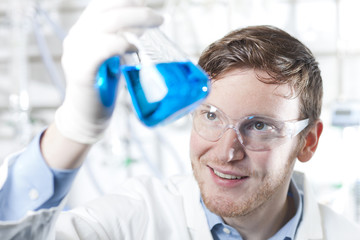 Deutschland, junger Wissenschaftler, der blaue Flüssigkeit in Erlenmeyerkolben