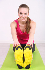 Young beautiful fitness girl exercising on green mat, in gym