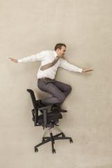 Geschäftsmann Skaten auf Bürostuhl