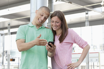 Deutschland, Düsseldorf, Junges Paar schaut Handy an