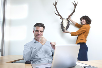 Geschäftsmann, der Laptop, während Assistent Aufhängen Trophäe für ihn