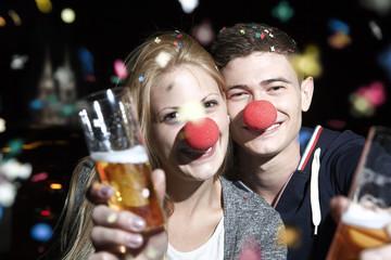 Deutschland, Köln, junges Paar mit Clowns Nasen Toasten