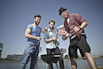 Deutschland, Köln, Junge Männer um Grill und Bier trinken