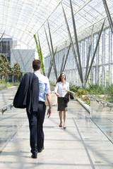 Geschäftsmann und Unternehmerin laufen in modernen Bürogebäude