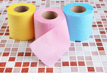 Color toilet paper rolls on bright background