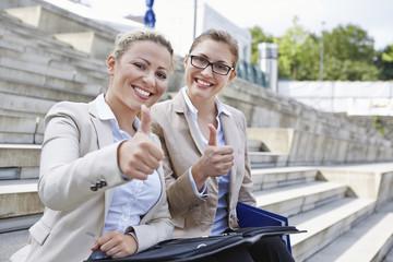 Deutschland, Köln, Zwei Geschäftsfrauen sitzen auf Treppen, die Daumen nach oben