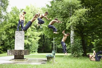 Deutschland, Bayern, Junger Mann springt vom Brunnen