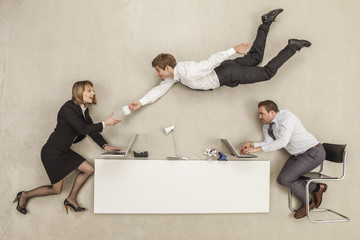 Geschäftsleute arbeiten, während ein anderer Geschäftsmann Bereitstellung Tasse
