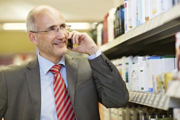 Deutschland, Köln, Mann sprechen über Handy im Supermarkt