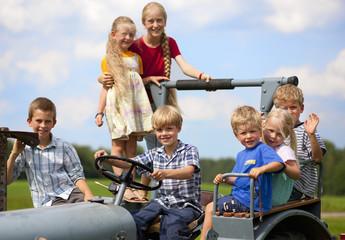 Deutschland, Bayern, Gruppe der Kinder sitzen in alten Traktor