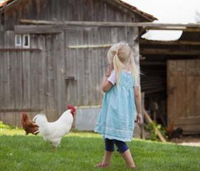 Deutschland, Bayern, Mädchen mit Huhn auf dem Bauernhof
