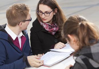 Drei Schüler lernen gemeinsam im Freien