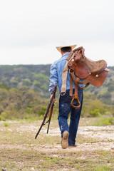 Texas, Cowboy zu Fuß mit Gewehr und Sattel
