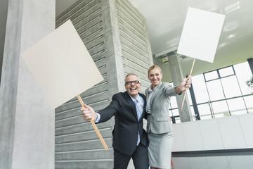 Deutschland, Stuttgart, Businessleute halten leere Schilder in Büro