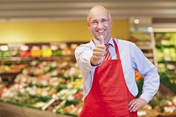Deutschland, Köln, Mann zeigt Daumen nach oben im Supermarkt