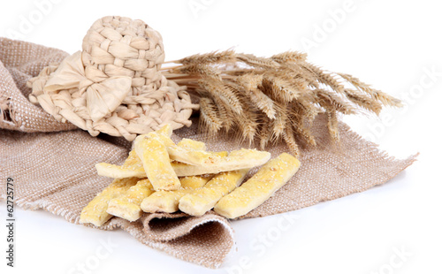 Tasty bread sticks on sackcloth isolated on white