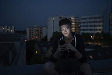 Junger Mann mit Smartphone sitzt auf Flachdach bei Nacht