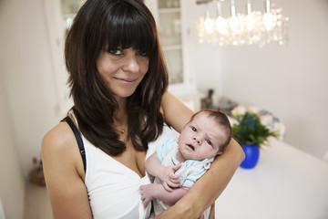 Lächelnde junge Mutter mit ihrem neugeborenen Sohn in den Armen
