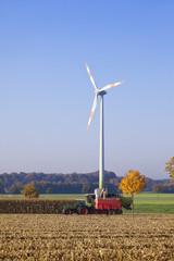 Deutschland, NRW, Ansicht der Windturbine mit Erntefahrzeug in der Nähe von Coesfeld