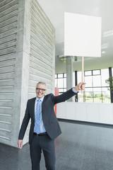 Deutschland, Stuttgart, Geschäftsmann hält Plakat im Büro