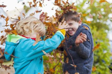 Zwei kleine Jungen werfen Blätter im Herbst