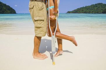 Thailand, Koh Surin Insel, Frau mit Krücken küssen Mann am weißen Sandstrand