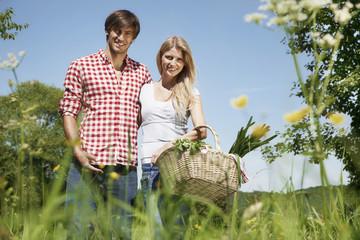 Deutschland, Köln, Junges Paar mit Picknick-Korb auf der Wiese