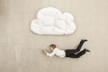 Geschäftsfrau mit Handy und unter Wolke Form Kissen fliegen