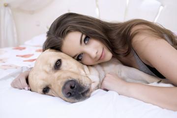 Mädchen liegt auf dem Bett mit ihrem Hund