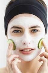 Deutschland, München, junge Frau mit Gurkenmaske