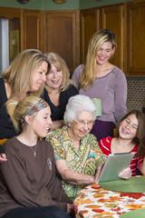 alte Frau mit Tablet-Computer unter ihre Familie