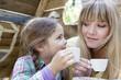 Deutschland, Köln, Mutter und Tochter trinken Tee, lächelt