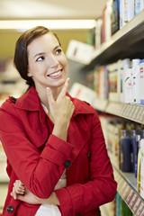 Deutschland, Köln, jungen Frau denkt nach im Supermarkt