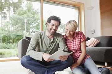 Deutschland, Nürnberg, Senioren Paar mit Tablet PC im Wohnzimmer