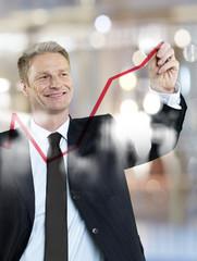 Geschäftsmann Zeichnung rote Kurve in Glasscheibe
