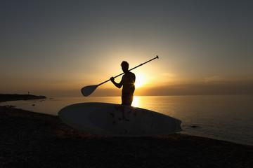 Deutschland, Schleswig Holstein, Mann mit Stand Up Paddle Board an der Ostsee