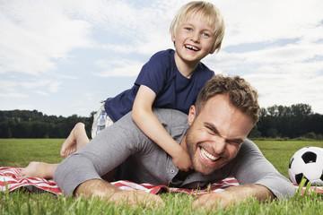 Deutschland, Köln, Vater und Sohn, spielen auf Picknickdecke