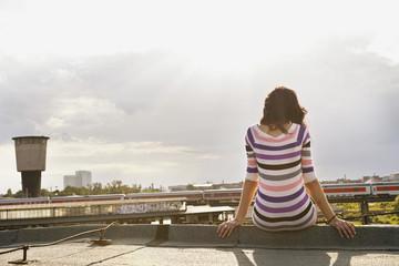 Deutschland, Hamburg, Junge Frau sitzt am Rand der Dach