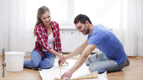 smiling couple measuring wallpaper