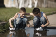 two little boys playing with paper boats in puddle
