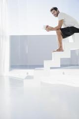 Spanien, Mann sitzt auf der Treppe mit Tasse