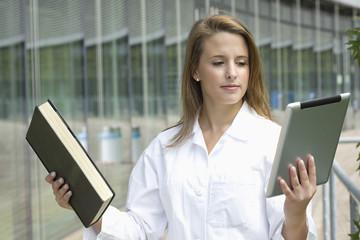 Deutschland, Düsseldorf, Medizinstudent Vergleich Buch mit Tablet PC