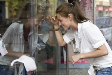 Deutschland, Köln, Junge Frau bei Fensterbummel