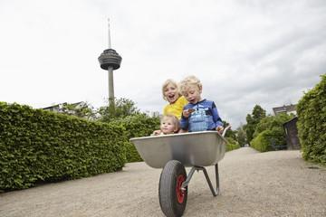 Deutschland, Köln, Jungen und Mädchen in der Schubkarre