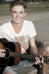 Deutschland, junger Mann spielt Gitarre im Park