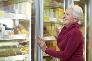 Deutschland, Köln, Seniorin, am Gefrierfach im Supermarkt
