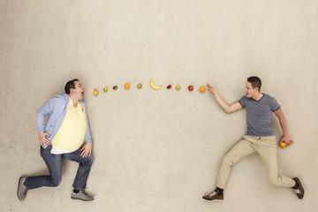 Mann wirft Früchte in einer anderen mans Mund