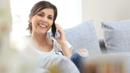 Young cheerful woman in couch talking on mobile phone
